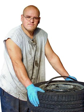 Royalty free photo print of an auto mechanic looking at the camera while working on a tire Stock Photo