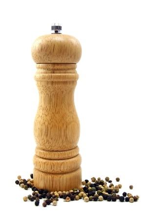 A wooden peppermill with peppercorns on white background photo
