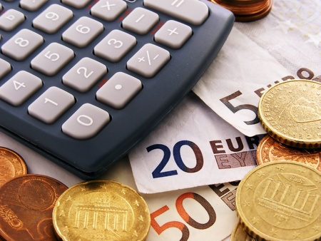 Close up of a calculator with euro money notes & coins photo