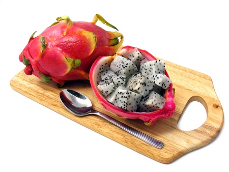 Diced dragon fruit pieces in the shell on a wooden board photo