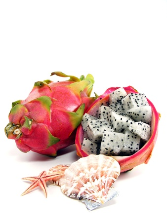Diced dragon fruit pieces in the shell fruit with sea shells photo