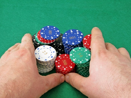 A player pushing a stack of poker chips on a green felt background photo
