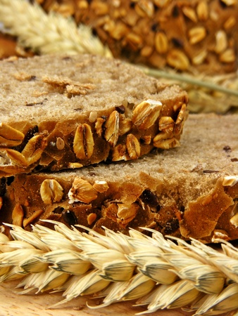 Brown bread & wheat on a wooden board photo