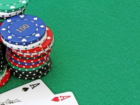 cartas de poker: A cerca de un par de ases y fichas de póquer en un fieltro verde de fondo