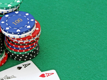 A close up of a pair of aces & poker chips on a green felt background photo