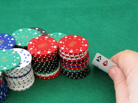 texas hold'em: A poker player seeing that he has been dealt a pair of aces