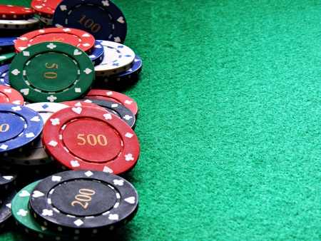 casino table: a selection of poker chips on a green felt table with copy space
