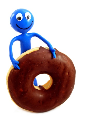 A blue bendy toy figure diving into a chocolate doughnut photo