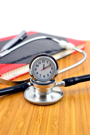 health check: Stethoscope with clock on a doctors table. Health check concept Stock Photo