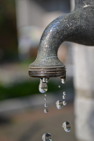 A garden water faucet tap with water drops photo