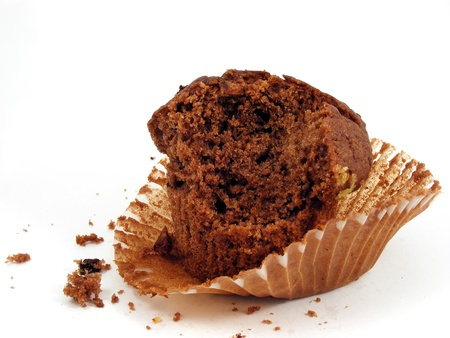 eaten: A half eaten chocolate muffin on the paper tray it was baked in. Stock Photo