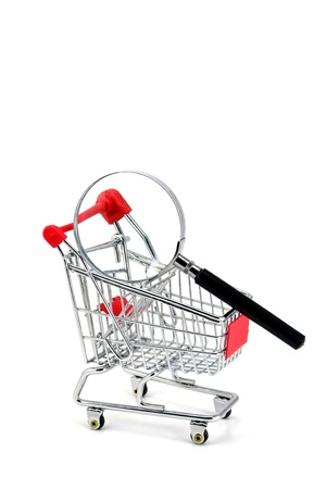 Consumer protection concept. Magnifying glass & shopping trolley photo