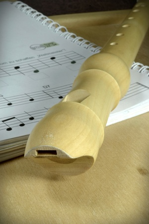 blow hole: A wooden recorder on a book of sheet music Stock Photo