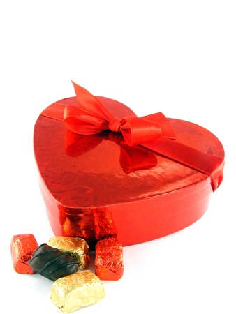 A shiny red love heart gift box with red ribbon & chocolates Stock Photo - 12033531