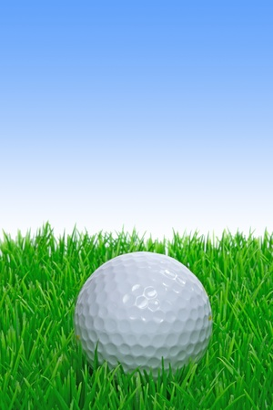 A single golf ball on grass with blue sky copy space photo