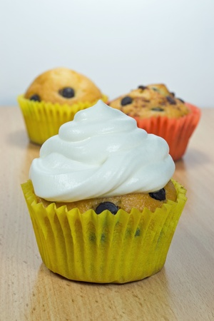whipped cream: A chocolate chip muffin with fresh cream on top Stock Photo