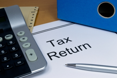 tax law: Tax return papers lying next to folder and calculator