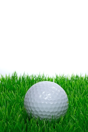 A golf ball sitting on grass with white background copy space