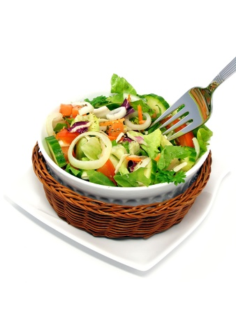 A mixed salad in a basket on a white background photo