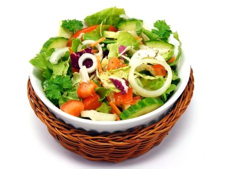 Una ensalada mixta en una cesta sobre un fondo blanco