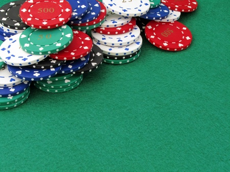 A selection of various valued poker chips on a green felt background with copy space photo