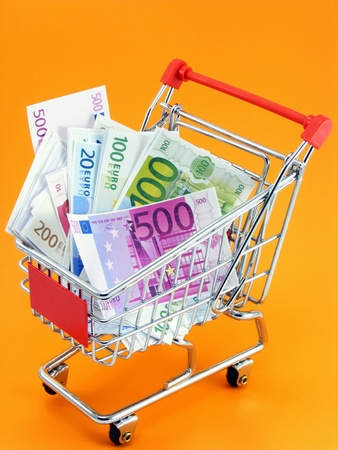 shopping trolley: A selection of euro currency in a shopping trolley on an orange background Stock Photo