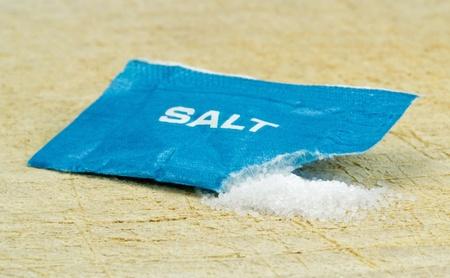 An open salt sachet with strewn salt on a wooden board  photo