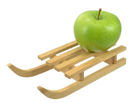 A green apple on a sleigh with white background Stock Photo - 13187869