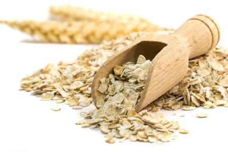 avena en hojuelas: La harina de avena copos con cuchara de madera sobre fondo blanco