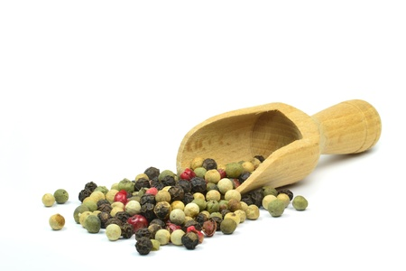Pepper corns and wooden scoop on white background