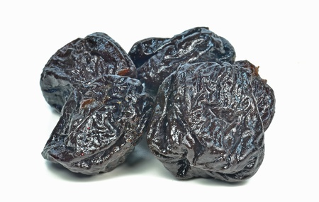 A selection of dried plums prunes on white background photo