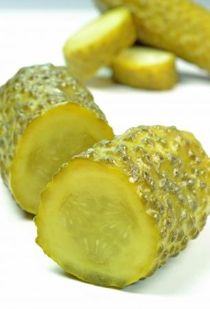 encurtidos: Un grupo de pepinillos en vinagre sobre un fondo blanco