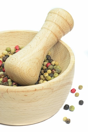 morter: A wooden mortar and pestle with pepper corns on white background