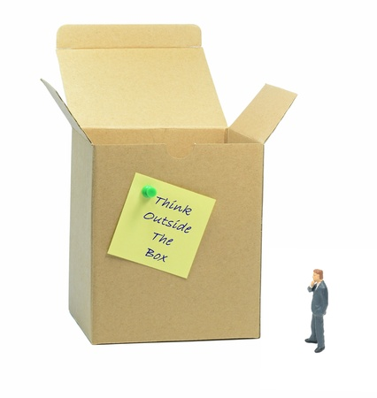 Think outside the box metaphor with businessman looking at box photo
