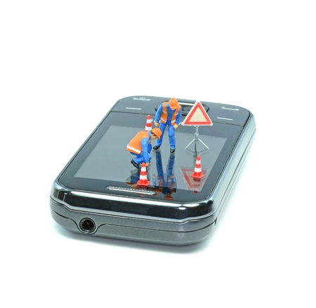 cell damage: Mini workmen inspecting scratches on a mobile cell phone display