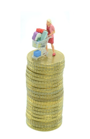 Woman with shopping cart trolley on a pile of coins photo