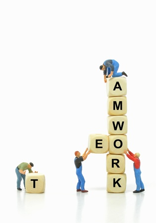 miniature people: Mini workmen in teamwork concept with copy space Stock Photo