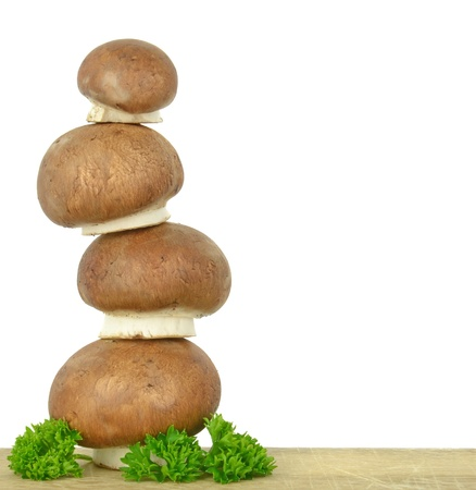 A tower of brown mushrooms on a wooden board with copy space photo