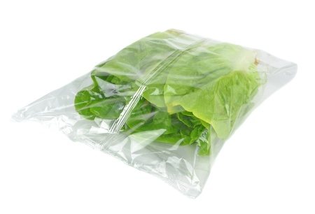 green leafy vegetables: A sealed plastic bag of lettuce on a white background