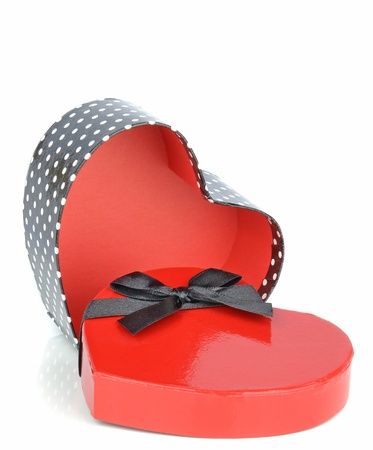 A love heart shaped gift box with bow on white background photo