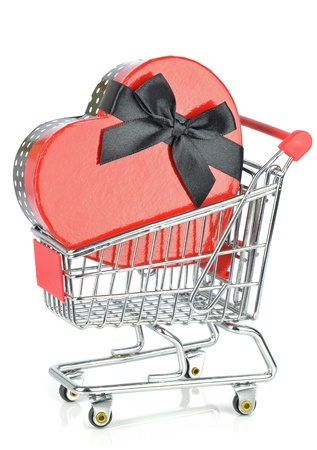 A love heart gift box in a shopping cart trolley on white background  photo
