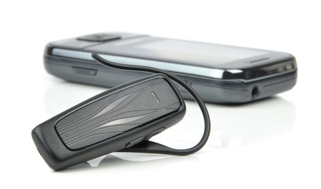A bluetooth headset and mobile cell phone on white background photo