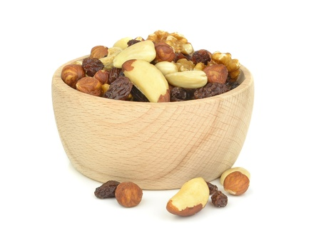 energy mix: A wooden bowl of mixed fruit and nuts on white background Stock Photo