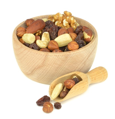 A wooden bowl of mixed fruit and nuts on white background photo
