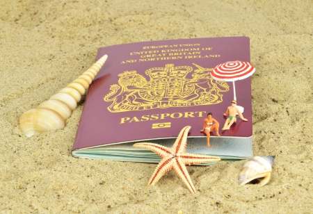 british people: A British passport on the beach with mini holiday makers Stock Photo