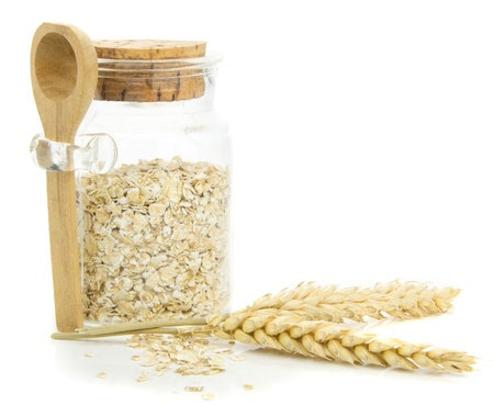 avena en hojuelas: Un tarro de copos de avena y trigo sobre un fondo blanco