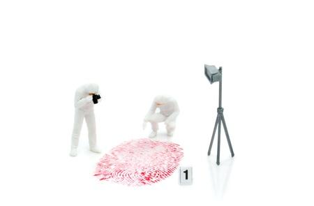 investigators: Miniature crime investigators photographing a finger print