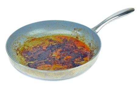 gebrannt: Eine sehr schmutzige Pfanne auf einem wei�en Hintergrund