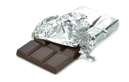 A bar of chocolate in tin foil wrapper on white background photo