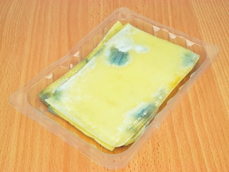 perishable: Slices of rotten mouldy cheese on a wooden background